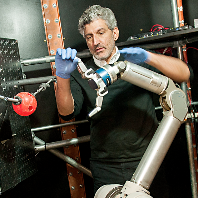 Faculty member working on a robotic arm
