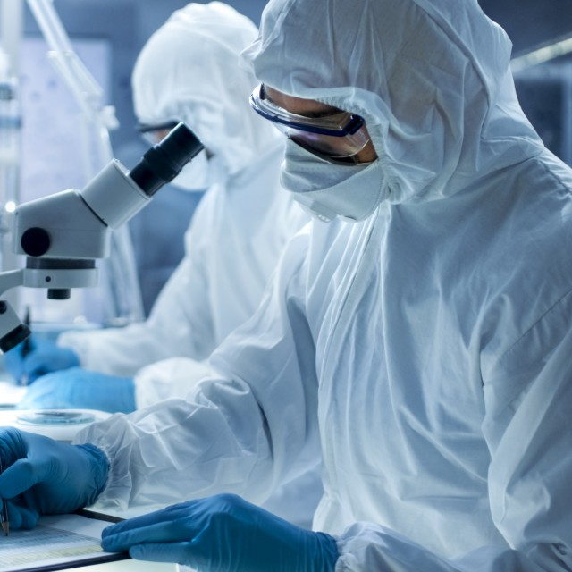 Scientists wearing protective suits in the lab